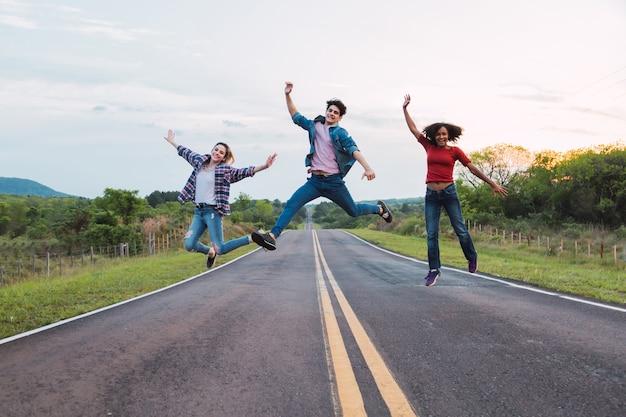 Jeunes amis sautant sur la route