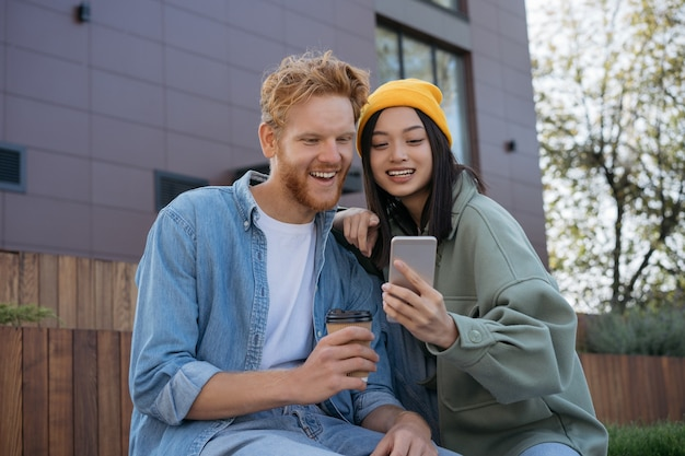 Jeunes amis souriants à l'aide de téléphone mobile, regarder des vidéos shopping en ligne