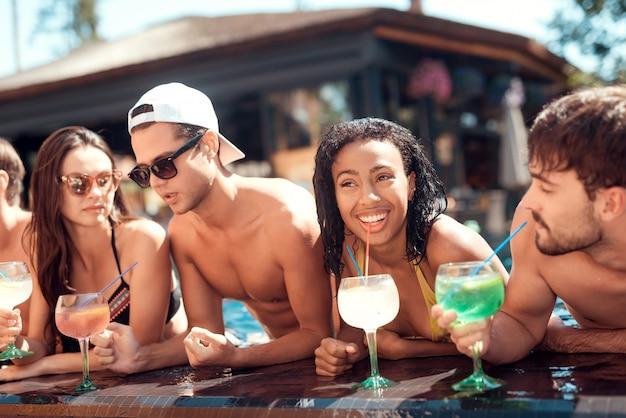 Jeunes amis souriants avec des cocktails au bord de la piscine