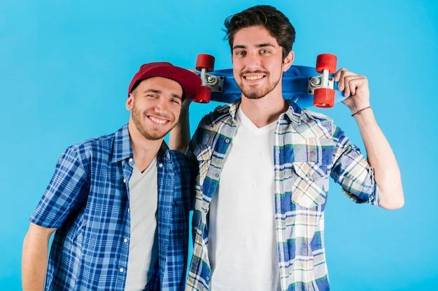 Jeunes amis souriants avec penny skateboard