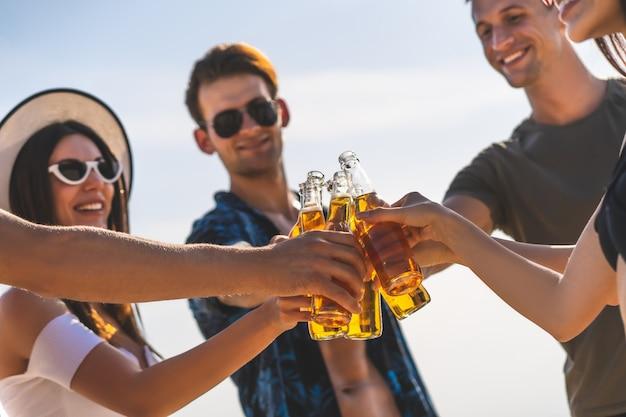 Les jeunes amis tenant des bouteilles de bière à la fête sur la plage