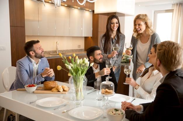 Jeunes amis en train de dîner à la maison et de porter un toast au vin blanc