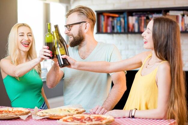 Jeunes amis vêtus avec désinvolture de t-shirts colorés s'amusant à faire tinter des bouteilles avec de la bière et de la pizza à la maison