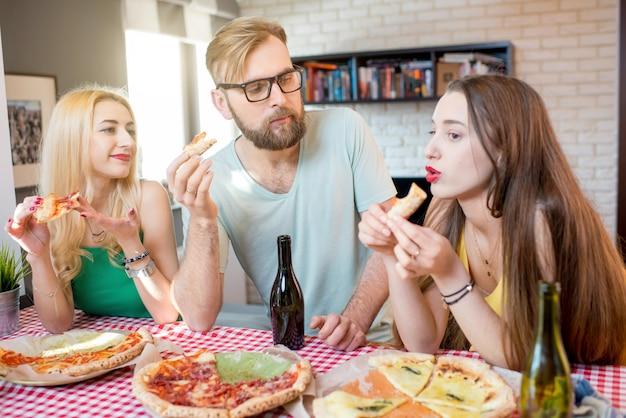 Jeunes amis vêtus avec désinvolture de t-shirts colorés en train de déjeuner avec pizza et bière à la maison