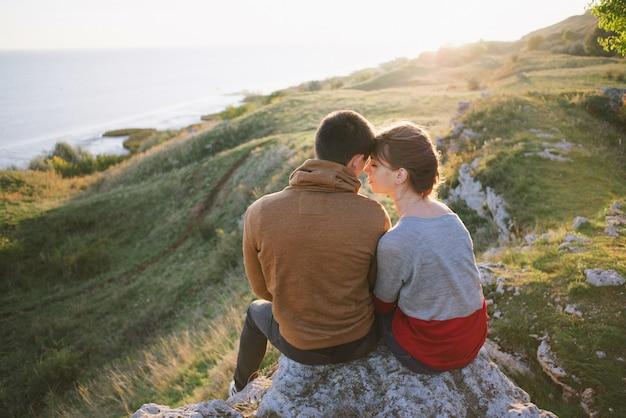 Jeunes amoureux au coucher du soleil dans les montagnes