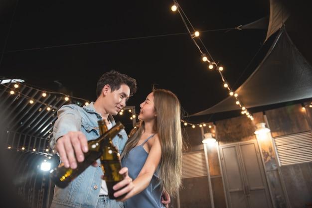 Les jeunes amoureux d'un couple asiatique s'amusent à danser et à boire dans la soirée sur le toit de la boîte de nuit au sol, tenant une bouteille de bière et un contact visuel flirtant à la fête du couple.