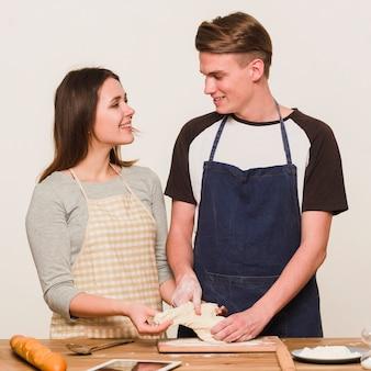 Jeunes amoureux pétrir la pâte ensemble