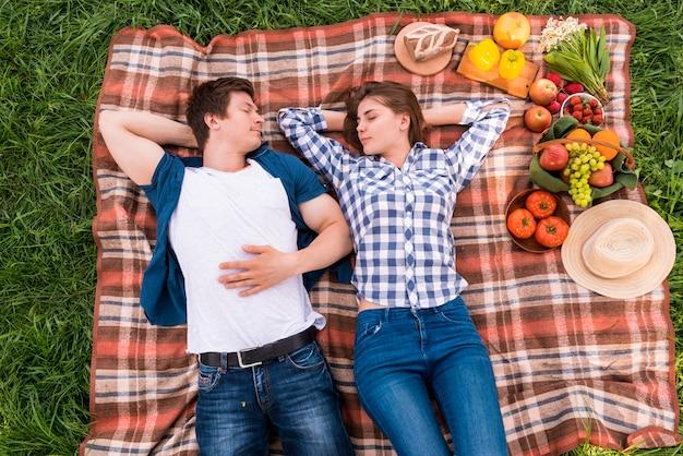 Jeunes amoureux prenant la sieste sur une couverture à l'extérieur