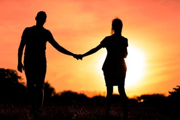 Jeunes amoureux se tenant la main au coucher du soleil
