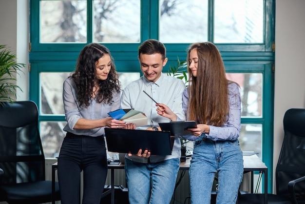 Jeunes architectes ou designers caucasiens utilisant la palette de couleurs pour un nouveau projet sur l'ordinateur portable dans le bureau moderne élégant avec grande fenêtre.