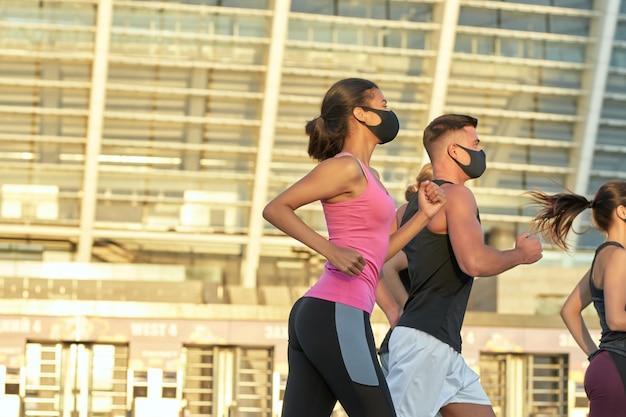 Jeunes athlètes de race mixte dans des masques courant latéralement