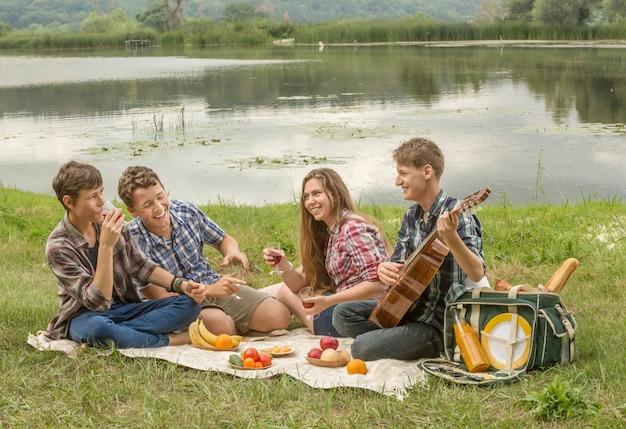 Jeunes ayant un pique-nique sur la plage de la rivière