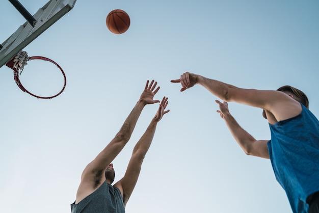 Jeunes basketteurs jouant en tête-à-tête sur un terrain extérieur. concept de sport et de basket-ball.