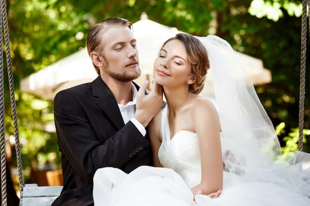 Jeunes beaux jeunes mariés souriant, appréciant, assis sur une balançoire dans le parc.