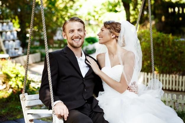 Jeunes beaux jeunes mariés souriant, riant, assis sur une balançoire dans le parc.