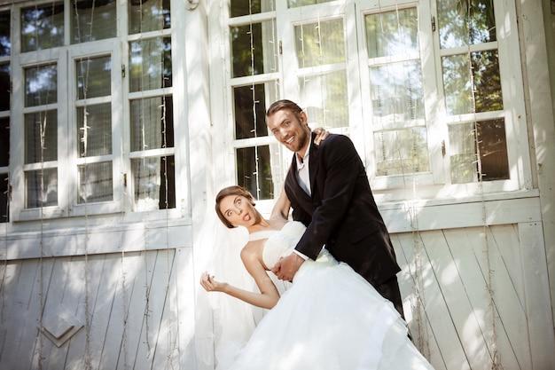 Jeunes beaux mariés habillés souriant, dupant, dansant à l'extérieur.