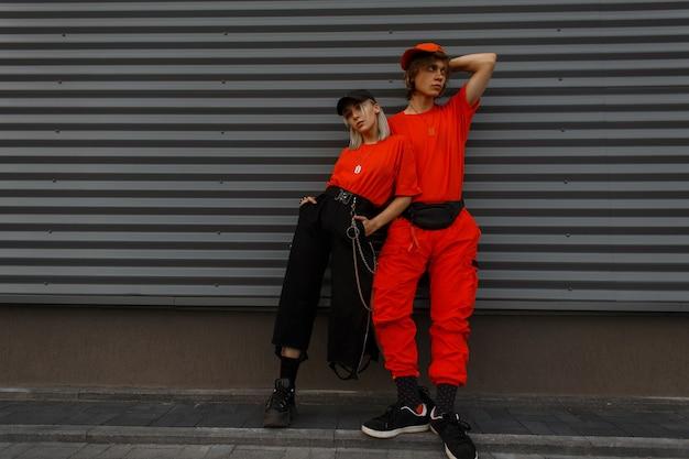 Jeunes beaux modèles de couple élégant dans des casquettes de mode et des vêtements orange à la mode se tiennent près du mur gris