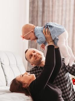 De jeunes beaux parents jouent avec leur bébé fille dans la chambre. famille heureuse