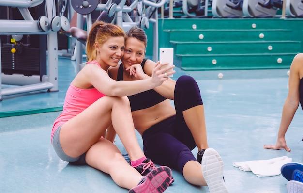 Jeunes belles amies prenant un selfie avec un smartphone assis sur le sol d'un centre de remise en forme après une dure journée d'entraînement
