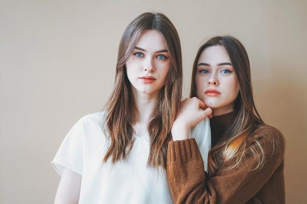 Jeunes belles cheveux longs filles soeurs jumelles en casual isolé sur fond beige
