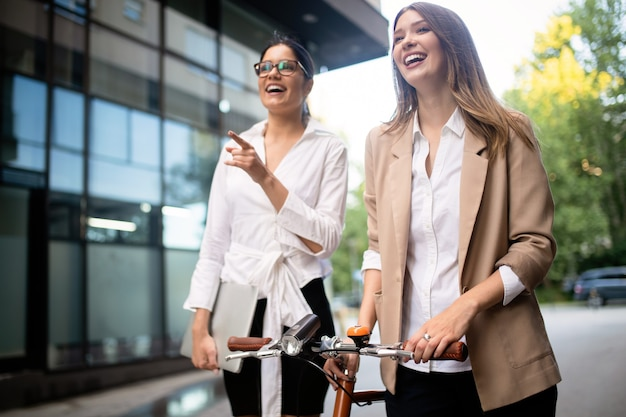 Jeunes belles femmes d'affaires heureuses parlant en plein air. immeuble de bureaux sur fond.