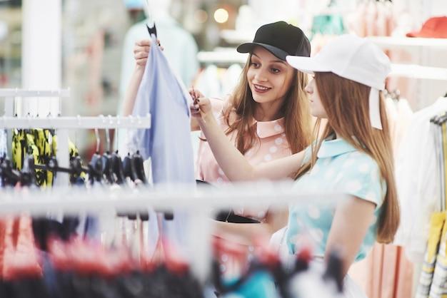 Jeunes belles femmes au marché hebdomadaire du tissu - les meilleurs amis partagent du temps libre en s'amusant et en faisant du shopping