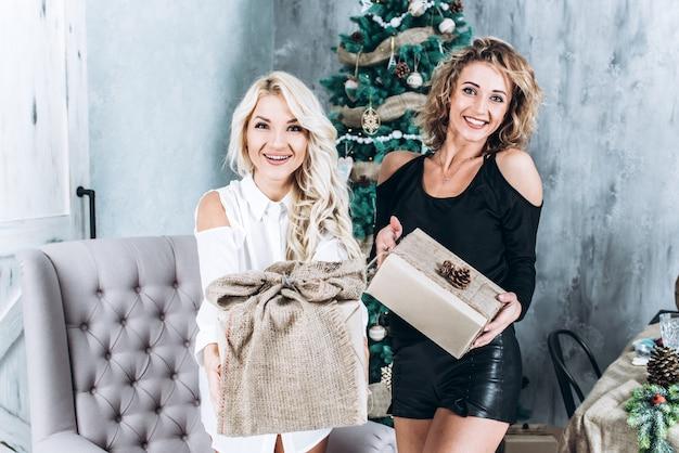 Jeunes belles femmes heureuses avec des boîtes-cadeaux debout près de sapin de noël