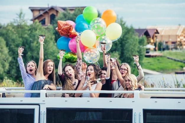 Jeunes belles femmes heureuses célèbrent l'enterrement de vie de garçon dans une limousine décapotable