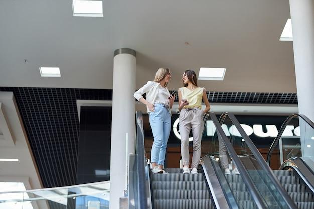 Jeunes belles femmes heureuses sur l'escalator du centre commercial