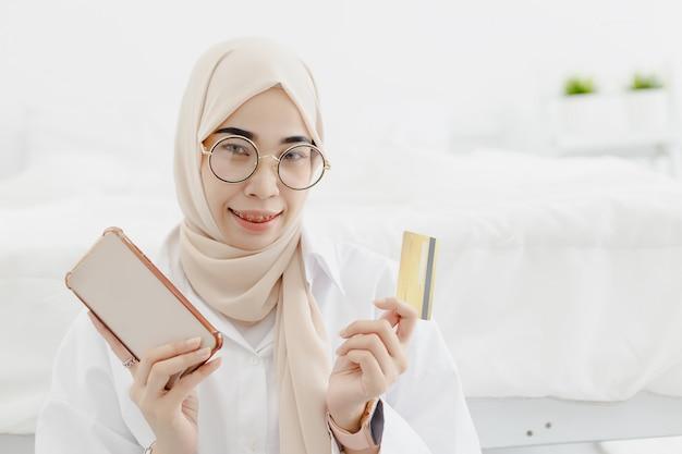 Jeunes belles femmes musulmanes portant le hijab avec sourire joyeux tenant la carte de crédit smartphone, concept de magasinage en ligne.