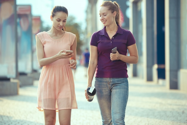 Jeunes belles femmes parlant sur téléphone mobile en plein air.