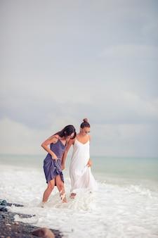 Jeunes belles femmes sur la plage s'amusent dans les eaux peu profondes