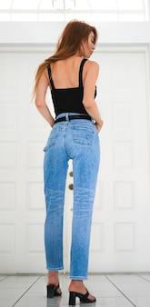 Jeunes belles femmes portant des jeans bleus et des hauts noirs posant un style différent