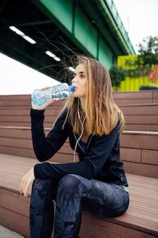 Jeunes belles femmes se reposant et buvant de l'eau après avoir fait des exercices