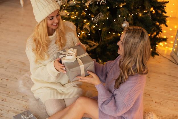 De jeunes belles filles heureuses dans un pull vintage et un bonnet tricoté donnent des cadeaux et s'assoient près de l'arbre de noël. vacances d'hiver en famille. bruyant