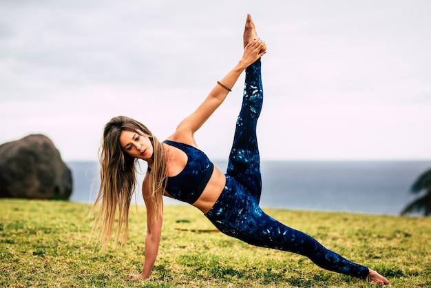 Jeunes belles personnes actives dans l'activité de position équilibrée de pilates en plein air