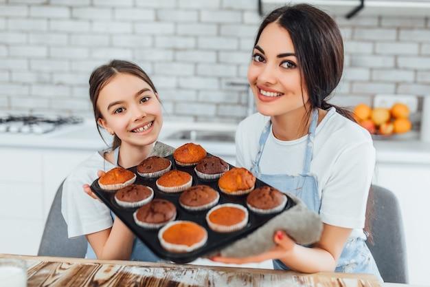 Jeunes belles soeurs avec des petits gâteaux