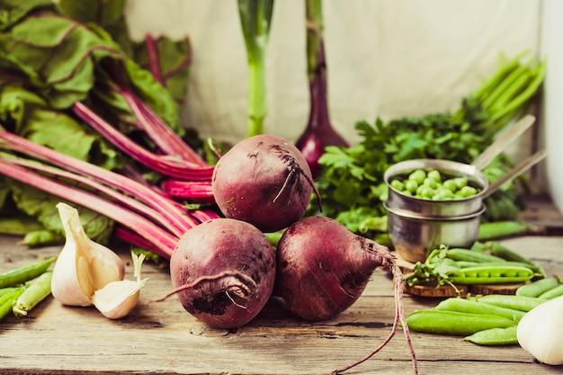 Jeunes betteraves biologiques, verts, ail sur une table en bois. légumes frais d'automne. mise au point sélective. concept d'aliments antioxydants sains et crus.