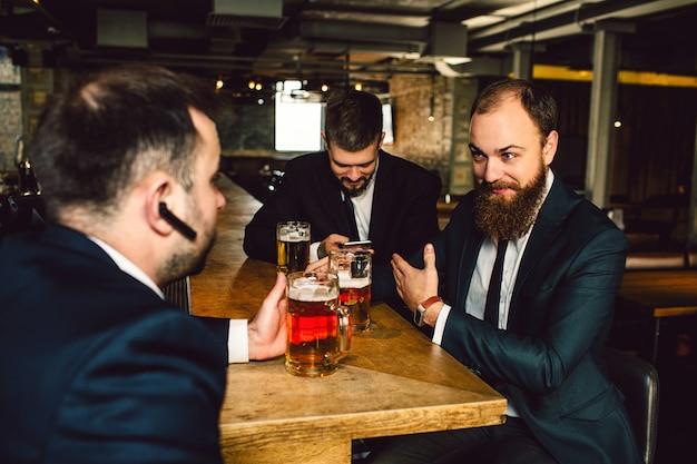 Les jeunes bsinessmen positifs en costume s'assoient ensemble à table. ils détiennent des chopes de bière. le gars devant a un casque noir dans l'oreille. les hommes sont en barre.