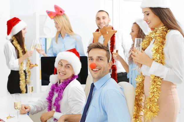 Jeunes célébrant noël à la fête d'entreprise au bureau