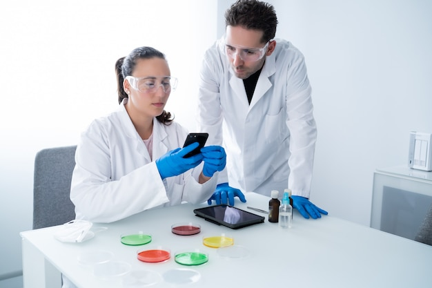 De jeunes chercheurs consultent des informations sur un smartphone à propos de leurs travaux de recherche dans une solution de boîte de pétri en laboratoire
