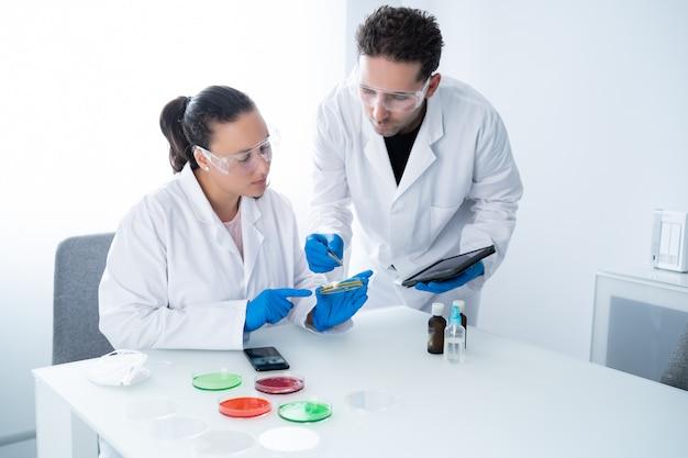 De jeunes chercheurs examinent une solution dans une boîte de pétri dans un laboratoire