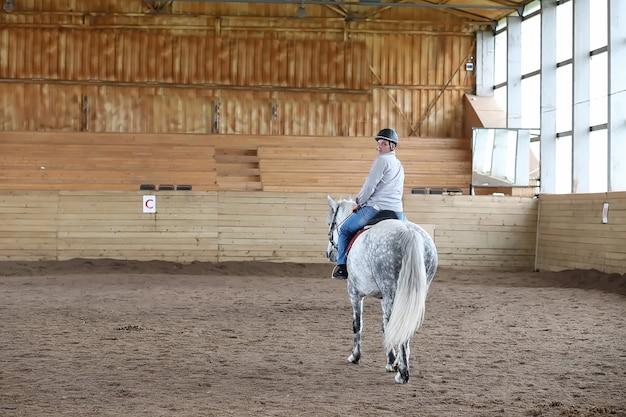 Jeunes sur un cheval s'entraînant dans une arène en bois