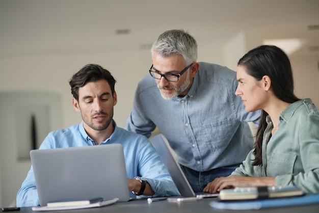 Jeunes collègues avec un ancien patron travaillant avec des ordinateurs