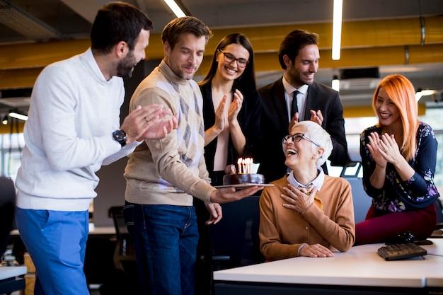 De jeunes collègues célèbrent l'anniversaire d'un collègue plus âgé au bureau et apportent un gâteau