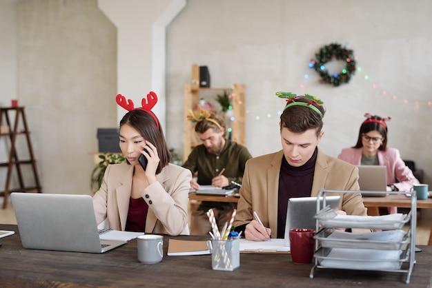 Jeunes collègues interculturels contemporains dans des vêtements décontractés intelligents et des bandeaux de noël en réseau devant des ordinateurs portables tout en étant assis en rangées