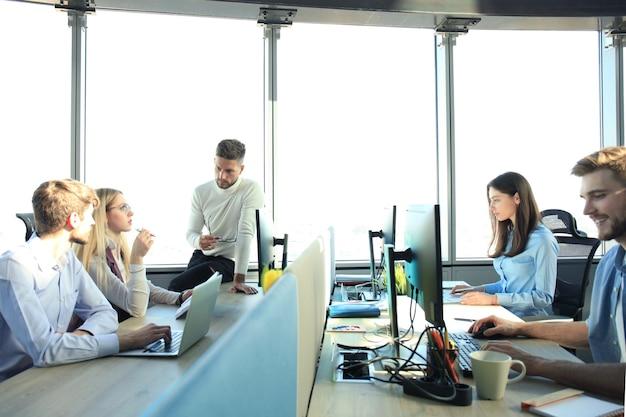 Jeunes collègues modernes en tenue décontractée élégante travaillant ensemble tout en passant du temps dans le bureau de création.