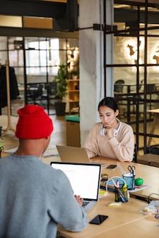 Jeunes collègues multiethniques féminins et masculins assis à table et travaillant sur des ordinateurs portables au bureau