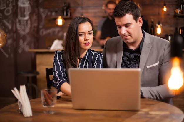 De jeunes collègues se rencontrent dans un café et s'entraident. travail sur ordinateur portable. débat d'affaires.