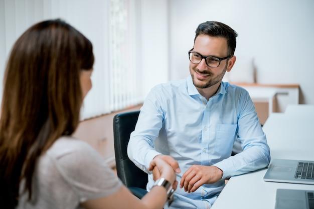 Jeunes collègues se serrant la main au bureau créatif